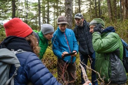 UAS researcher Eran Hood looks over a topographical map at the field site. (L to R: Kyra St. Pierre, Eran Hood, Ian Giesbrecht, Jason Fellman)